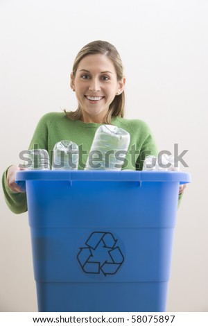 An attractive young woman his smiling and holding a blue recycle bin with plastic bottles in it. Vertical shot.
