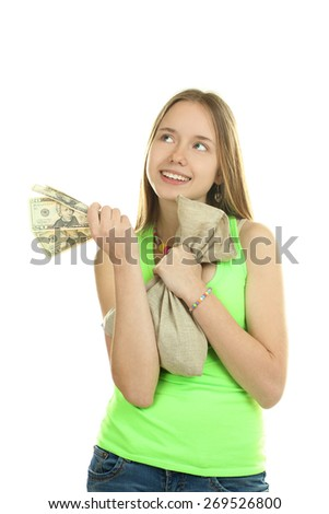 An attractive young woman holds up a bag of money while smiling at the camera - stock photo