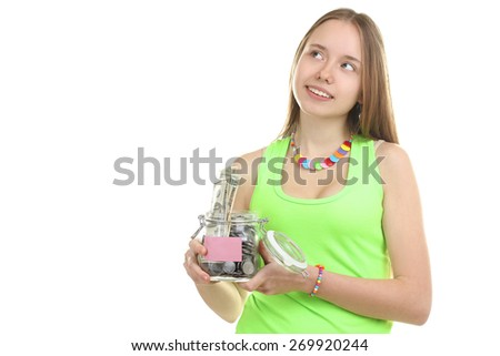 An attractive young woman holds up a jar of money vnile - stock photo