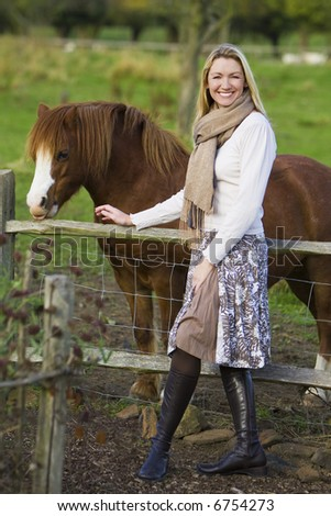 An attractive young woman in a countryside setting leans on a fence with a pony in the background