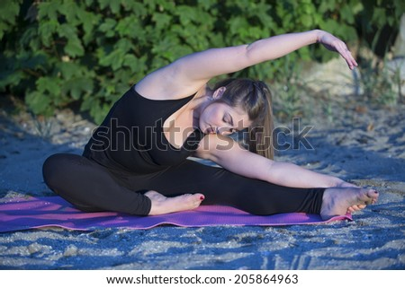 An attractive young woman in black spandex does yoga stretching on the beach.