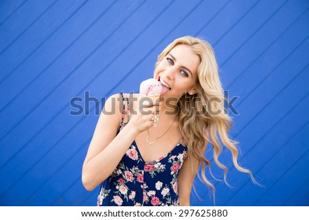An attractive young woman in her twenties enjoying an ice cream cone in front of a bright blue wall. She has long blond hair that is blowing in the wind. She looks like a California beach girl. - stock photo