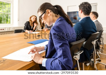 An attractive young woman is checking papers during a business meeting in a conference room - mixed caucasian team rather casual, ambiente might suggest a startup or an agency