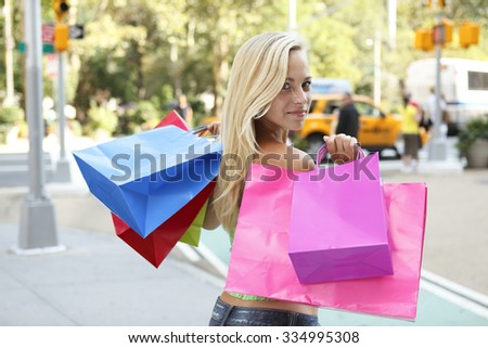 An attractive young woman looking back and carrying shopping bags over her shoulder.