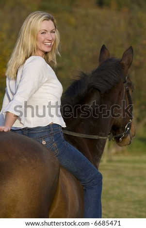 An attractive young woman riding a horse bareback during the fall