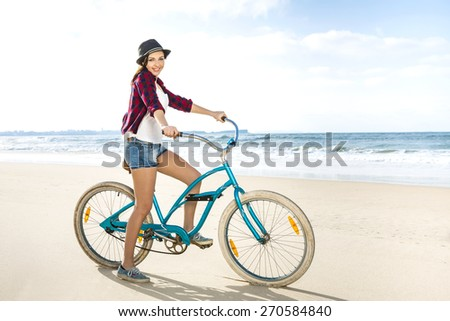 An attractive young woman riding her bicycle on the beach - stock photo