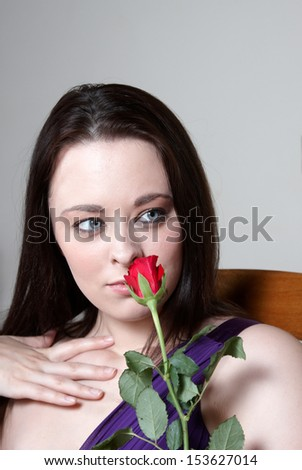 An attractive young woman smelling a red rose