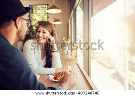 An attractive young woman talking with her boyfriend while sitting in a cafe table. Young couple at coffee shop. - stock photo