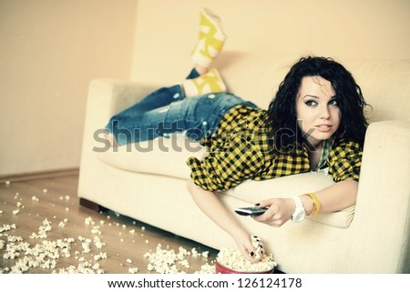 An attractive young woman watching TV - stock photo