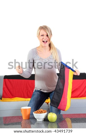 An attractive young woman whoops a german team while sitting at home and watching tv.