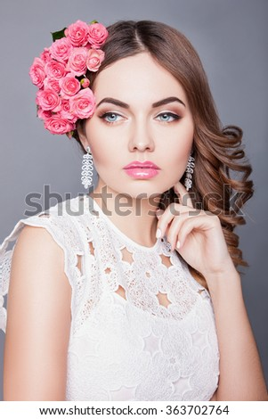 An attractive young woman with makeup on his face and flowers in her hair. Portrait of girl with dark hair on a gray background, beautiful makeup on her face - stock photo