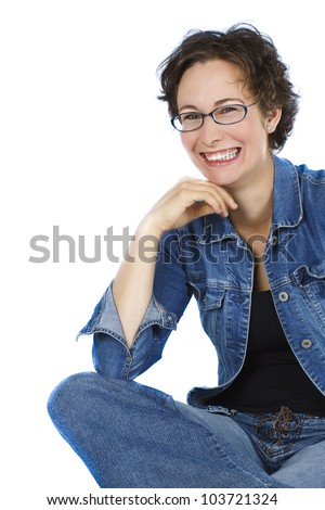 An attractive young woman with short brown hair, wearing glasses, blue jeans, black top, sitting cross-legged, is laughing very happily - isolated on white - stock photo