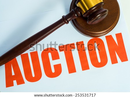 An auction sign and wooden mallet on a white background