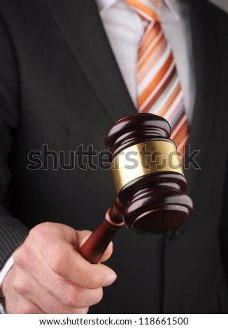 an auctioneer's hand is holding a wooden gavel