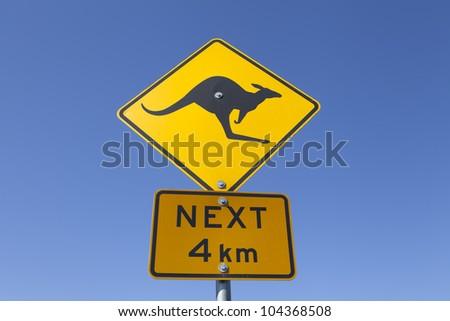 An Australian kangaroo warning road sign against a vibrant blue sky. - stock photo