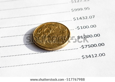An Australian one dollar coin on top of a balance sheet with various number. Financial background.