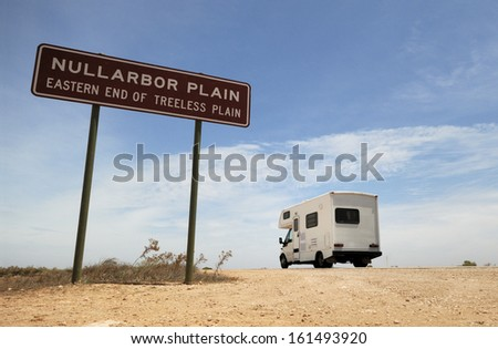An Australian Outback touring camper on the road in the Nullarbor Plain. - stock photo