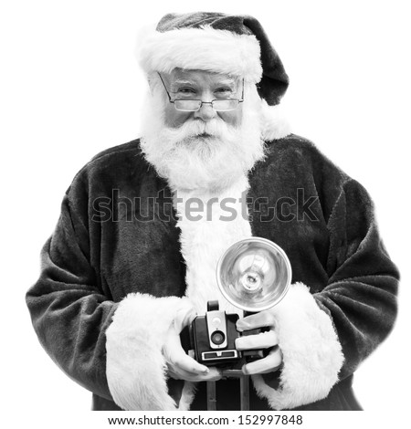 An authentic Santa Claus holds an old Vintage camera in black &white.  Perfect for Christmas Holiday greeting card  - stock photo