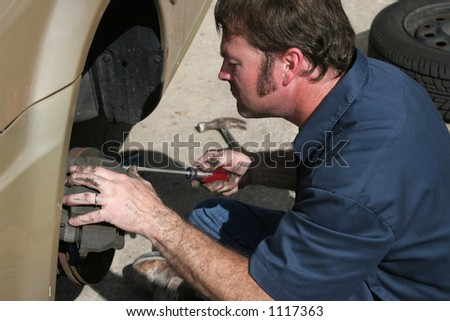 An auto mechanic inspecting the brake housing on a car. - stock photo