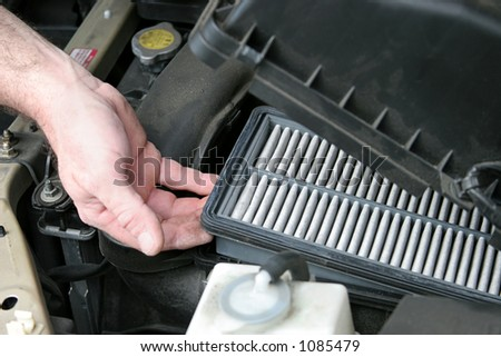 An auto mechanic removing the dirty air filter from an automobile. - stock photo