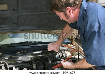 An auto mechanic using jumper cables on a car battery.  Horizontal with copy space for text. - stock photo