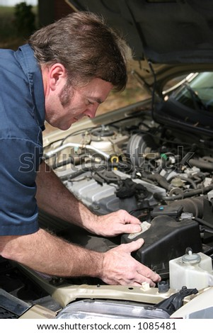 An auto mechanic working on a car.