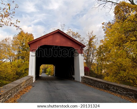 An Autumn view of a country road and the Cabin Run Covered Bridge located in Plumstead Township, Bucks County, Pa. - stock photo