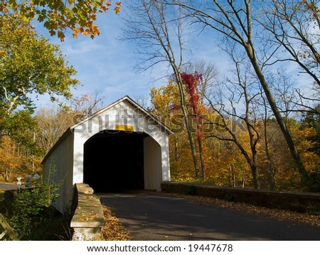 An Autumn view of the historic Loux Covered Bridge in rural Bucks County, Pennsylvania. - stock photo