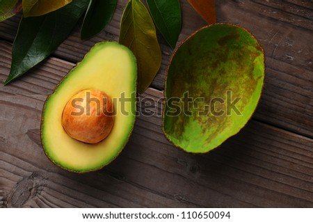 An Avocado cut in half on a wood surface with leaves. One half shows the seed while the other has been scooped out. - stock photo