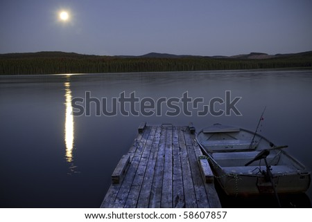 An awesome fishing lake is displayed with a bright moon reflecting off the water. - stock photo