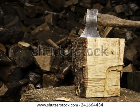 An axe sticking in a chunk of firewood in front of a staple of firewood - stock photo