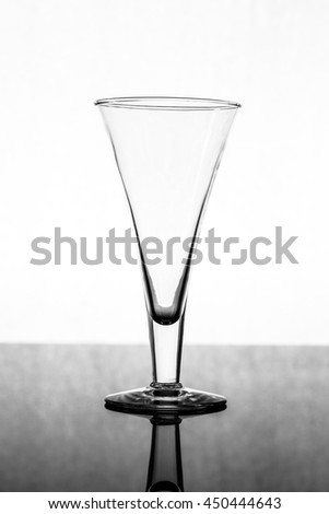 an black and white picture whit and empty glass
