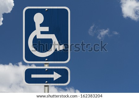 An Blue American road sign with a wheelchair and arrow with sky background, HandicapParking Sign - stock photo