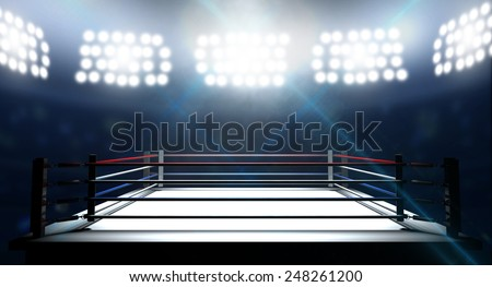 An boxing ring surrounded by ropes spotlit by floodlights in an arena setting at night - stock photo