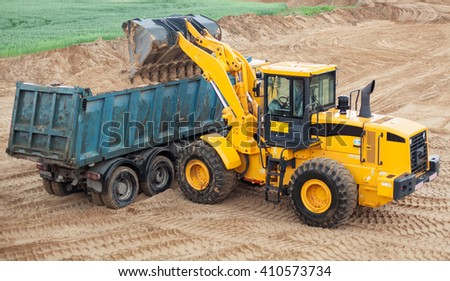 An dozer working removing earth on a construction site. - stock photo