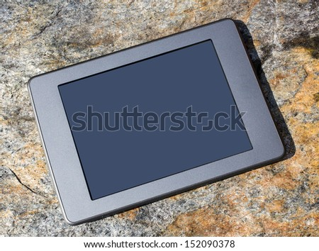 An e-book reading device outside against a stone background with blank screen for custom copy. - stock photo