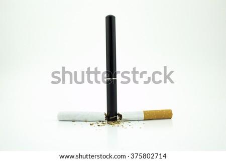 An e-cigarette standing between a broken cigarette - stock photo