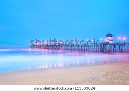 An early morning image of a pier in Huntington Beach, California using long shutter speeds to get motion blur on the water and a big blue sky. - stock photo