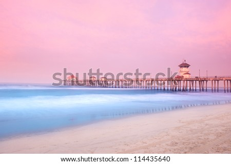 An early morning sunrise over a pier shows the pink cloud and light cover while using a slow shutter speed to capture water movement. - stock photo