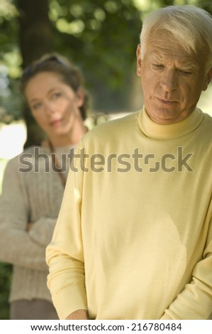 An earnest man, woman in the background. - stock photo