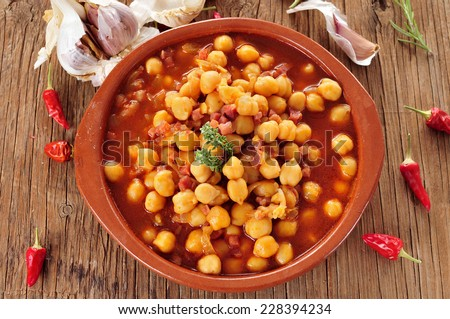 an earthenware bowl with potaje de garbanzos con jamon, a spanish chickpeas stew with ham, on a rustic wooden table - stock photo