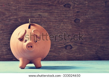 an earthenware piggy bank with a coin in his hole, on a blue rustic surface - stock photo