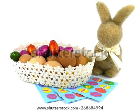 An Easter bunny and a basket with boiled chicken eggs and colourful eggs of chocolate - stock photo