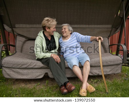 An edlerly mom sharing a laugh with her visiting daughter while sitting on a swing outdoors. - stock photo