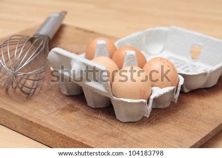 An egg-box with eggs and a whisk