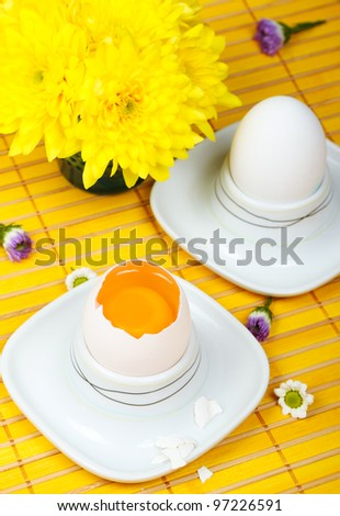 An egg in a white eggcup on yellow wooden placemat