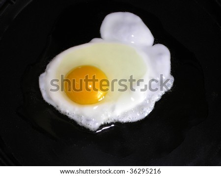 An egg is being cooked in a pan .