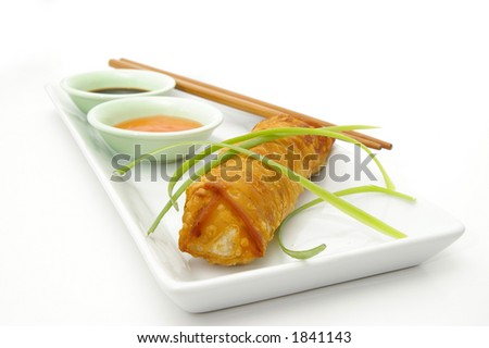 An egg roll appetizer with sauces and chopsticks.
