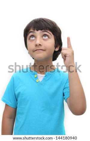 An eight year old boy looking up and pointing with one finger - stock photo