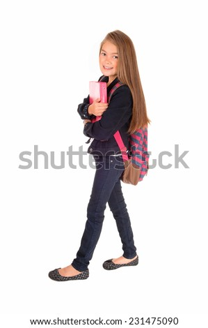 An eight year schoolgirl with her backpack over her shoulder standing for white background, holding her book.  - stock photo